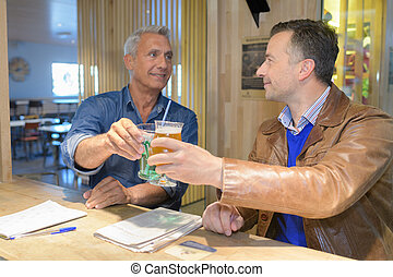 two men toasting a drink