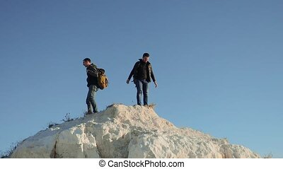 two men tourists hiking adventure climbers climb the...