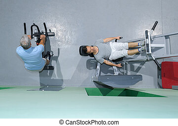 two men train with fitness machine