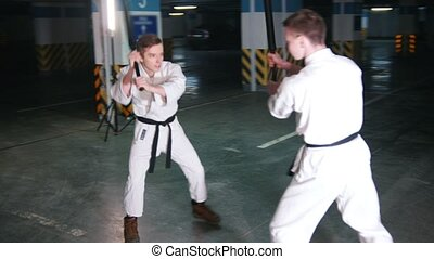 Two men training kendo on a parking lot. Mid shot