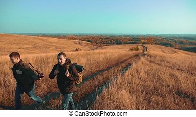 Two men traveler hiking with backpacks are walking along the path climbing into lifestyle the mountains. slow motion video. Tourist Hipster Hiker traveler on background view blue sky clouds go hiking trip adventure. hikers travel men with backpacks in the mountains concept