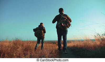 Two men traveler hiking with backpacks are walking along the...