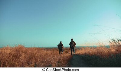 Two men traveler hiking with backpacks are walking lifestyle along the path climbing into the mountains. slow motion video. Tourist Hipster Hiker traveler on background view blue sky clouds go hiking trip adventure. hikers travel men with backpacks in the mountains concept
