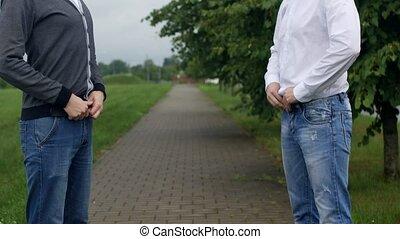 Two men unbutton their pants on the street, gays,...