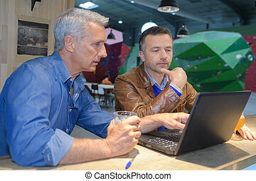 two men using a laptop in a cafe bar