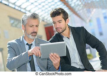 two men using digital table while having a break