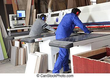 Two men using factory equipment