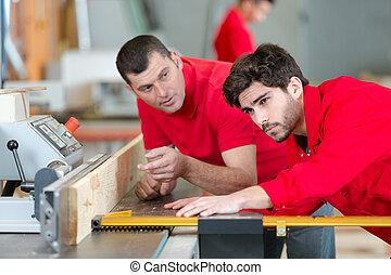 two men using woodworking machine