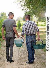 two men walking in vineyards