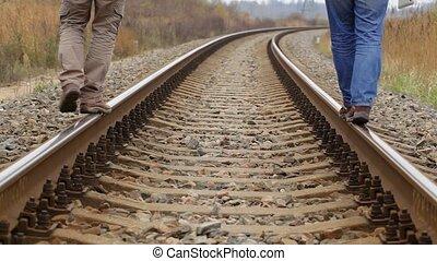 Two men walking on rail
