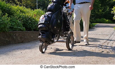 Two men walking with their golf caddies down a sand path