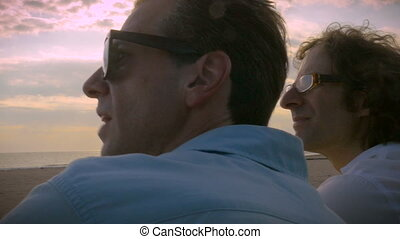Two men watching something on the beach overlooking a sunset...