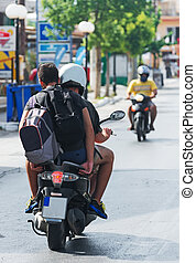 Two men with backpack on motorcycle. View from the back.