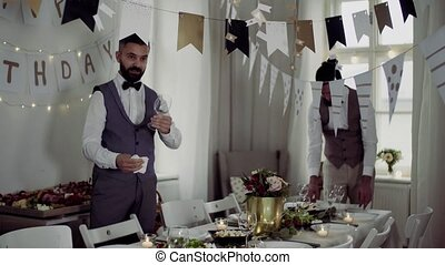 Two men with bows and vests setting a table for an indoor...