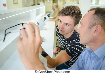 Two men with eyeglasses and microscopes