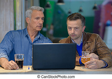 two men with laptop talking together and drinking
