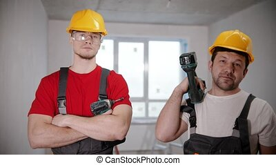 Two men workers standing in draft apartment holding instruments
