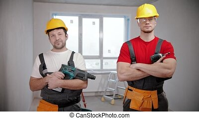 Two men workers standing in draft apartment holding their instruments