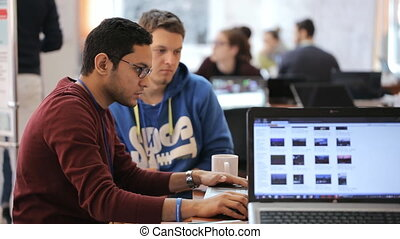 Two men working at the computer attentively, and discussing ...