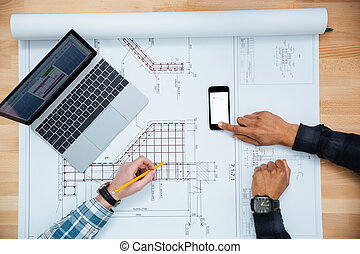 Two men working for blueprint using mobile phone and laptop