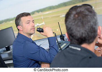 Two men working in airport control tower