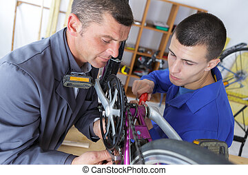 Two men working on bicycle