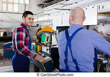 Two men working on machine
