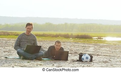 Two men working on the beach with a laptop slow motion video