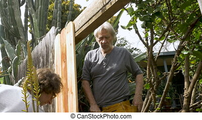 Two men working together repairing a broken fence measuring...