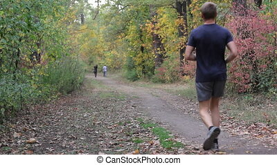 Two mens run in the park in autumn forest