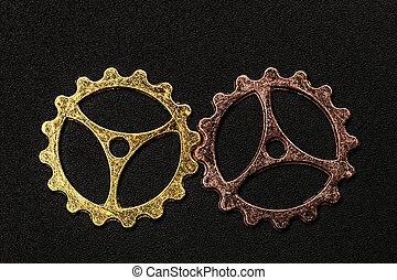 Two metal cogwheels interlocking.