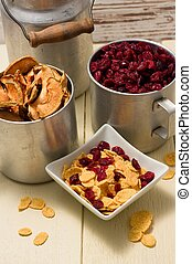 Two metal cups full of cranberries and dried apples