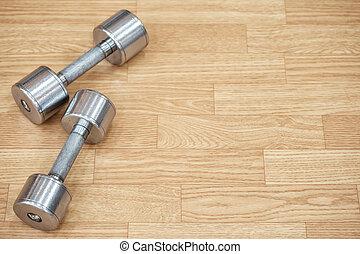 Two metal dumbbells on the floor