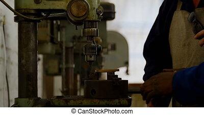 Two metalsmith using drill press machine in workshop 4k - ...