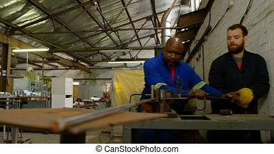 Two metalsmiths working in workshop 4k - Two metalsmiths ...