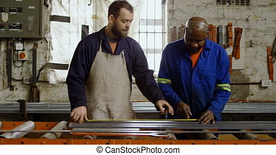Two metalsmiths working on machine 4k - Two metalsmiths ...