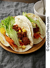 Two Mexican Tacos on a wooden plate