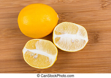 Two meyer lemons isolated on wood background
