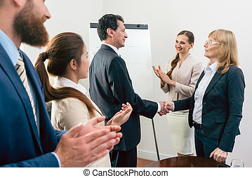 Two middle-aged business associates smiling while shaking hands
