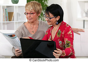 Two middle aged friends on a computer.