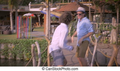 Two middle aged men friends having fun together on a wooden...