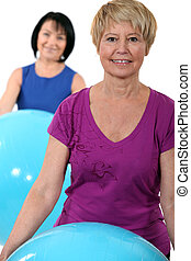 Two middle-aged women with gym balls