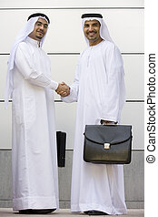 Two Middle Eastern businessmen holding briefcases