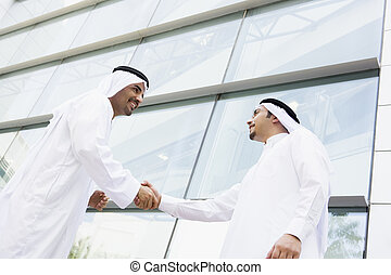 Two Middle Eastern businessmen shaking hands outside an office b