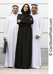 Two Middle Eastern businessmen standing with a woman
