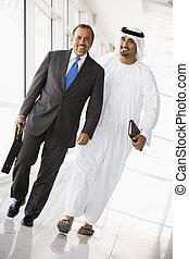 Two Middle Eastern businessmen walking in a corridor