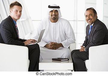 Two Middle Eastern men and a caucasian man talking at a...
