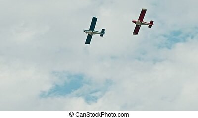Two military aircrafts flying in the cloudy sky - blue and red airplanes
