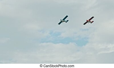Two military aircrafts flying in the sky - blue and red airplanes