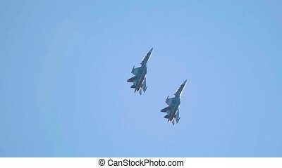 Two military fighter jets flying up in the blue sky. Mid...